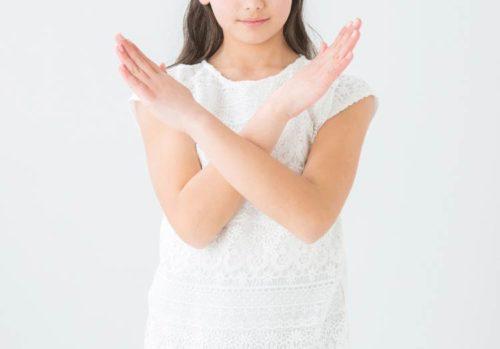 腕でバツ印を作っている女の子