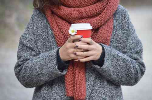 女性がコーヒをもってマフラーをしている写真