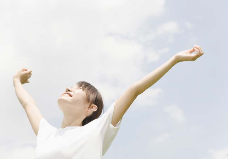 両腕を空に向かって広げ、スッキリした表情の女性