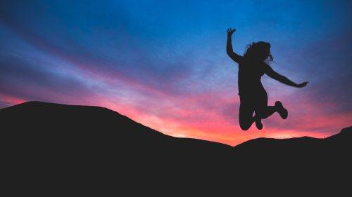 夜空を背景にジャンプしている女性の写真