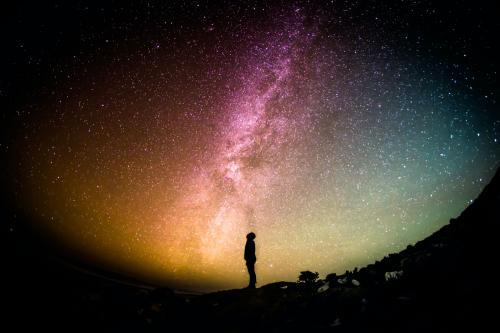 星空を背景にたたずむ男性のシルエット写真