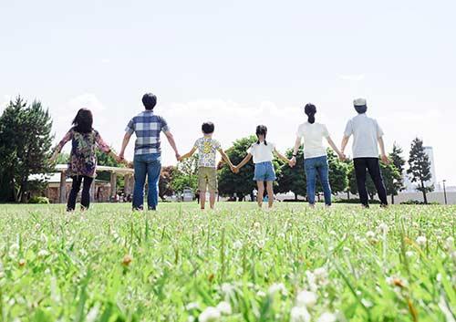 芝生の上に後ろ姿で並ぶ家族の写真