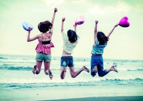 砂浜でジャンプしている女性3人の写真