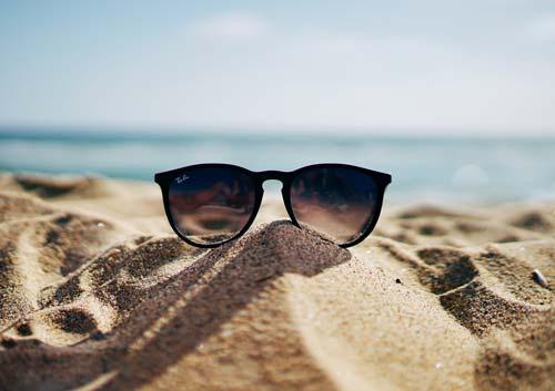 海を背景に砂浜の上にサングラスの写真