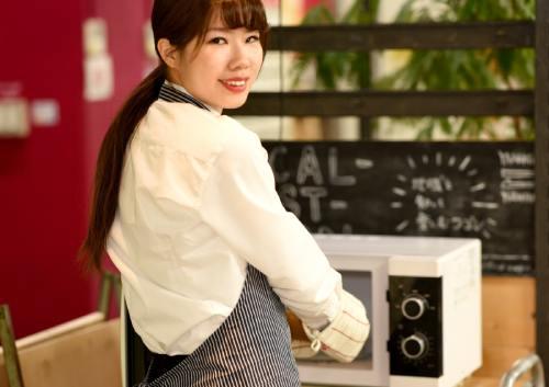電子レンジを使う女性の写真