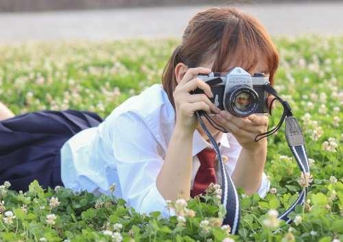 草むらでカメラをかまえる女子学生の写真