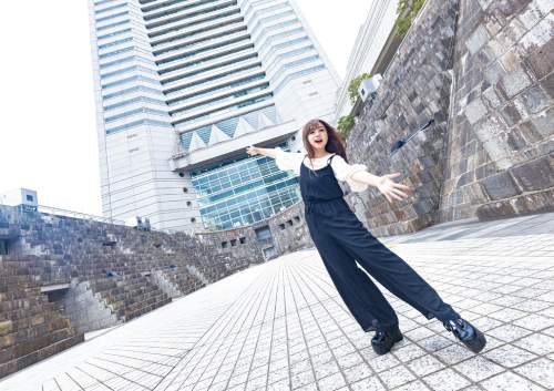 広角レンズで撮った女性とランドマークタワーの写真