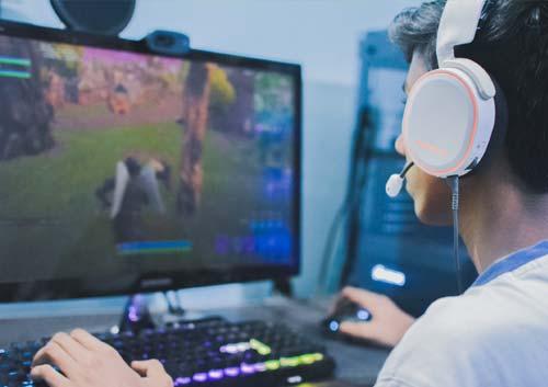 ヘッドフォンをしながらPCゲームをしている男性