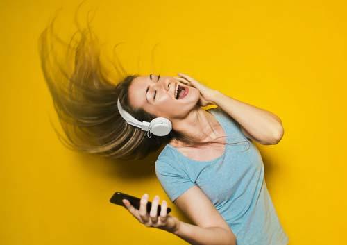 ワイヤレスヘッドホンで音楽を聞く女性