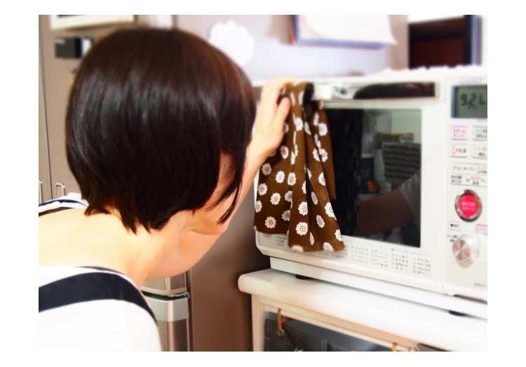 オーブンレンジを覗く女性