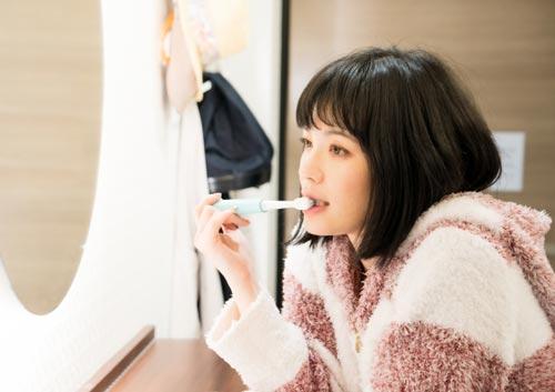 電動歯ブラシで歯を磨く女性の写真